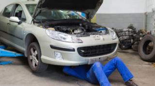 Male mechanic working under car at garage